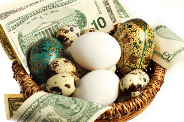 Close-up view of eggs, quail's, hen and artificial in a basket with US currency notes